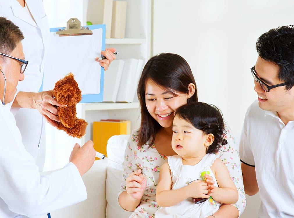 female nurse holding teddy to make the little kid calm